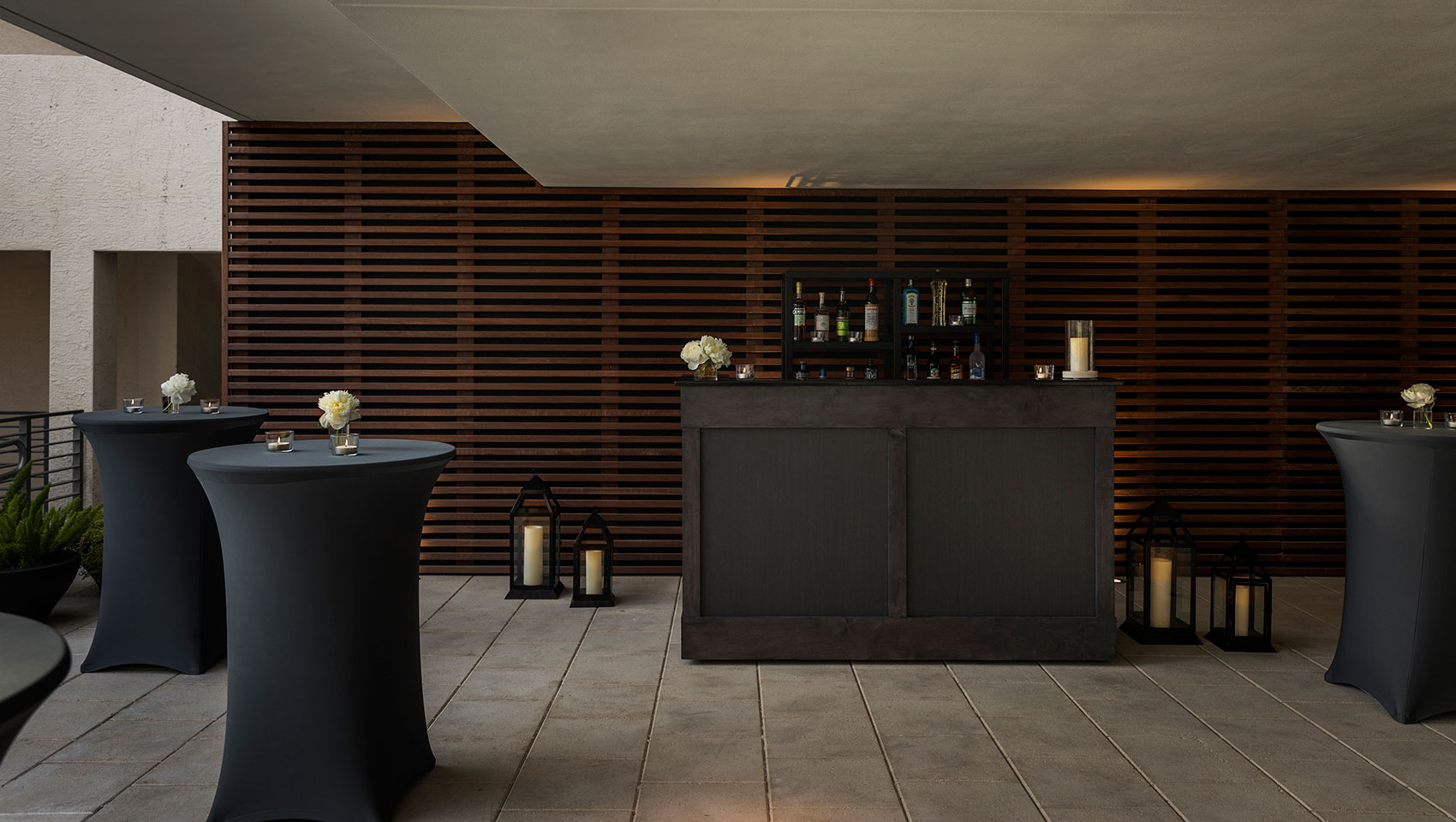 kimpton anglers breezeway with cocktail tables and a bar set for a social event